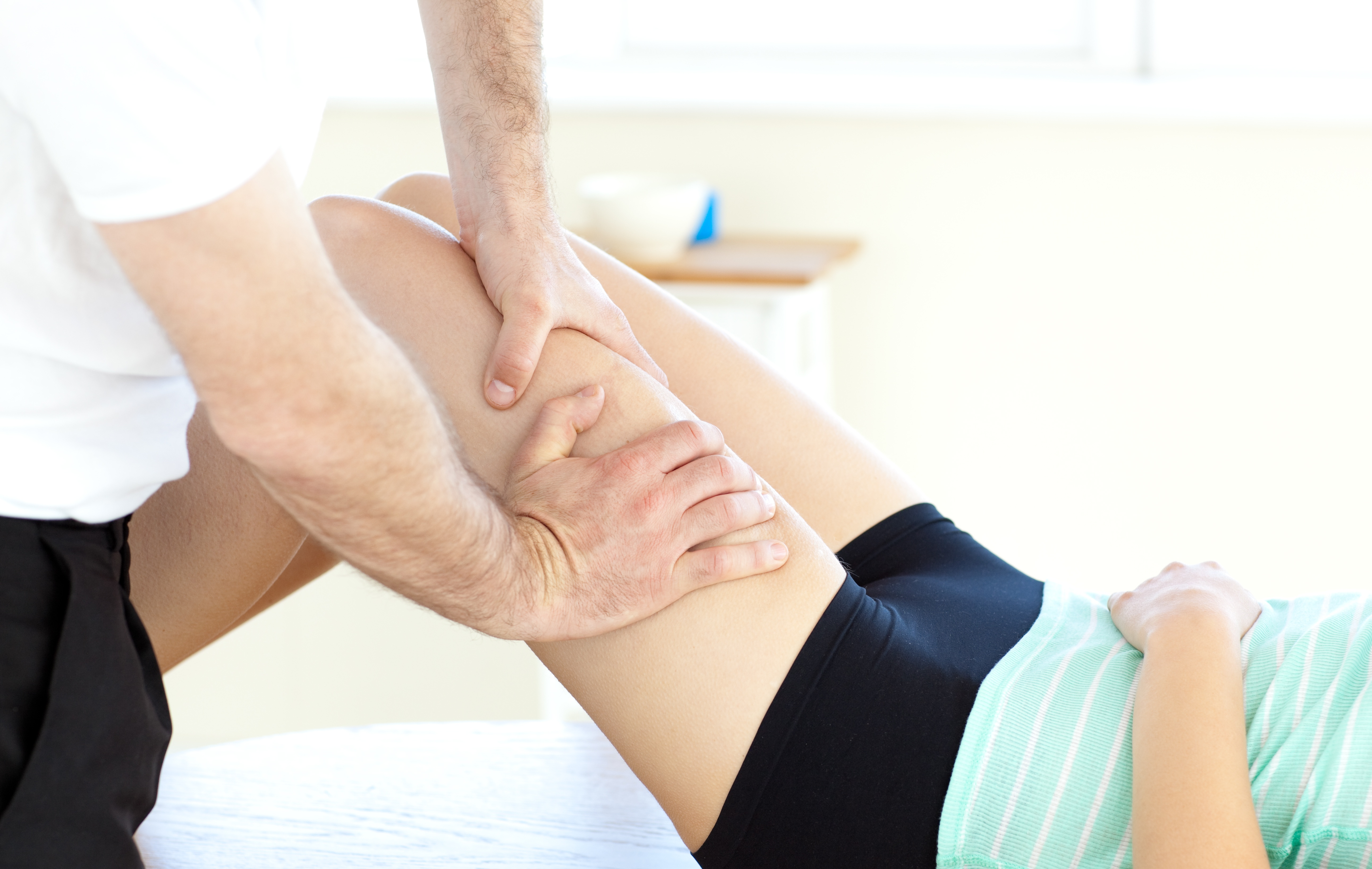 An athletic trainer massaging an athlete's injured leg