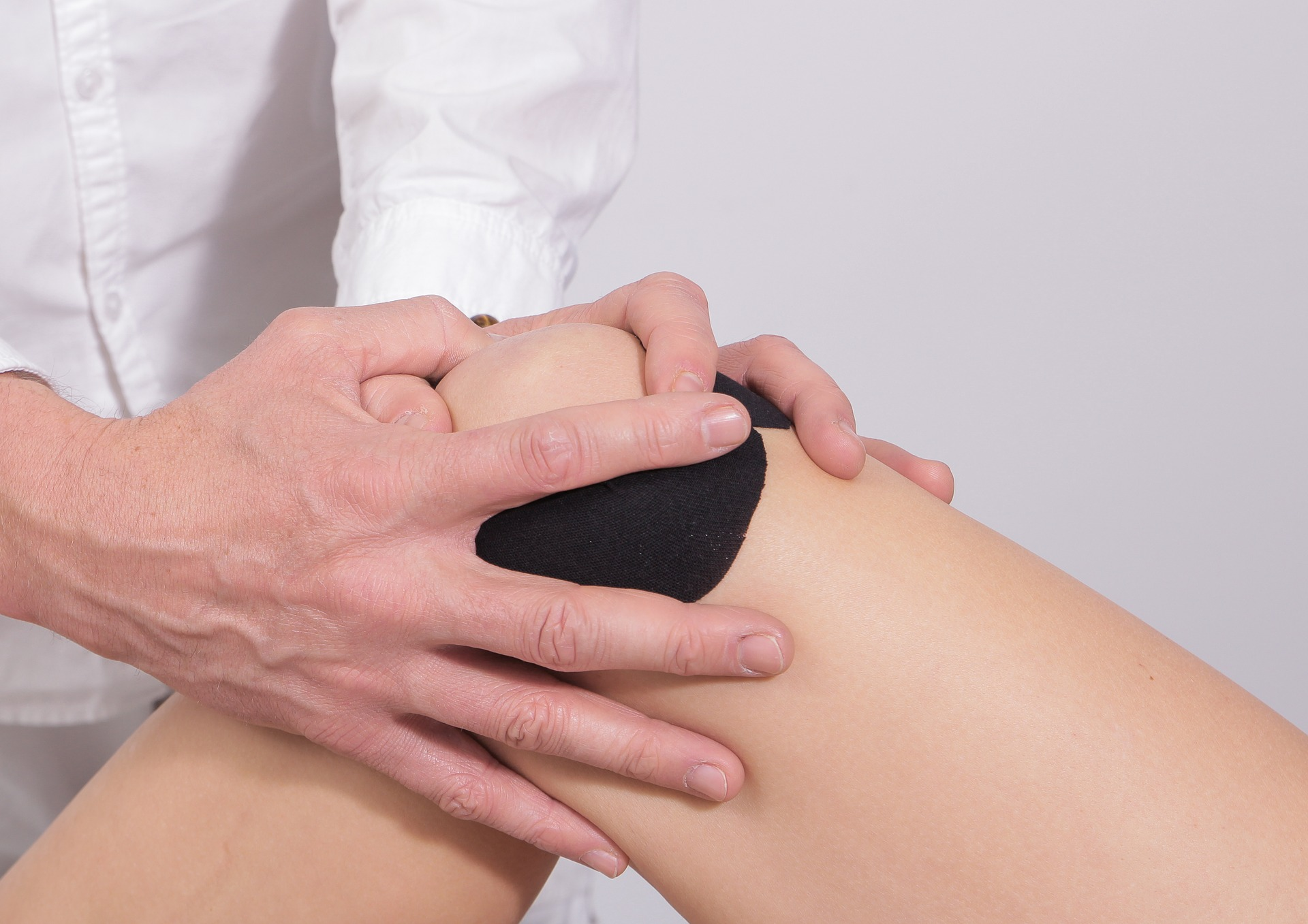 Athletic trainer wraps and treats injured knee