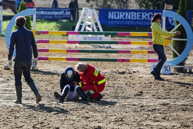 Athletic trainer quickly rushes from sidelines to help injured horseback rider