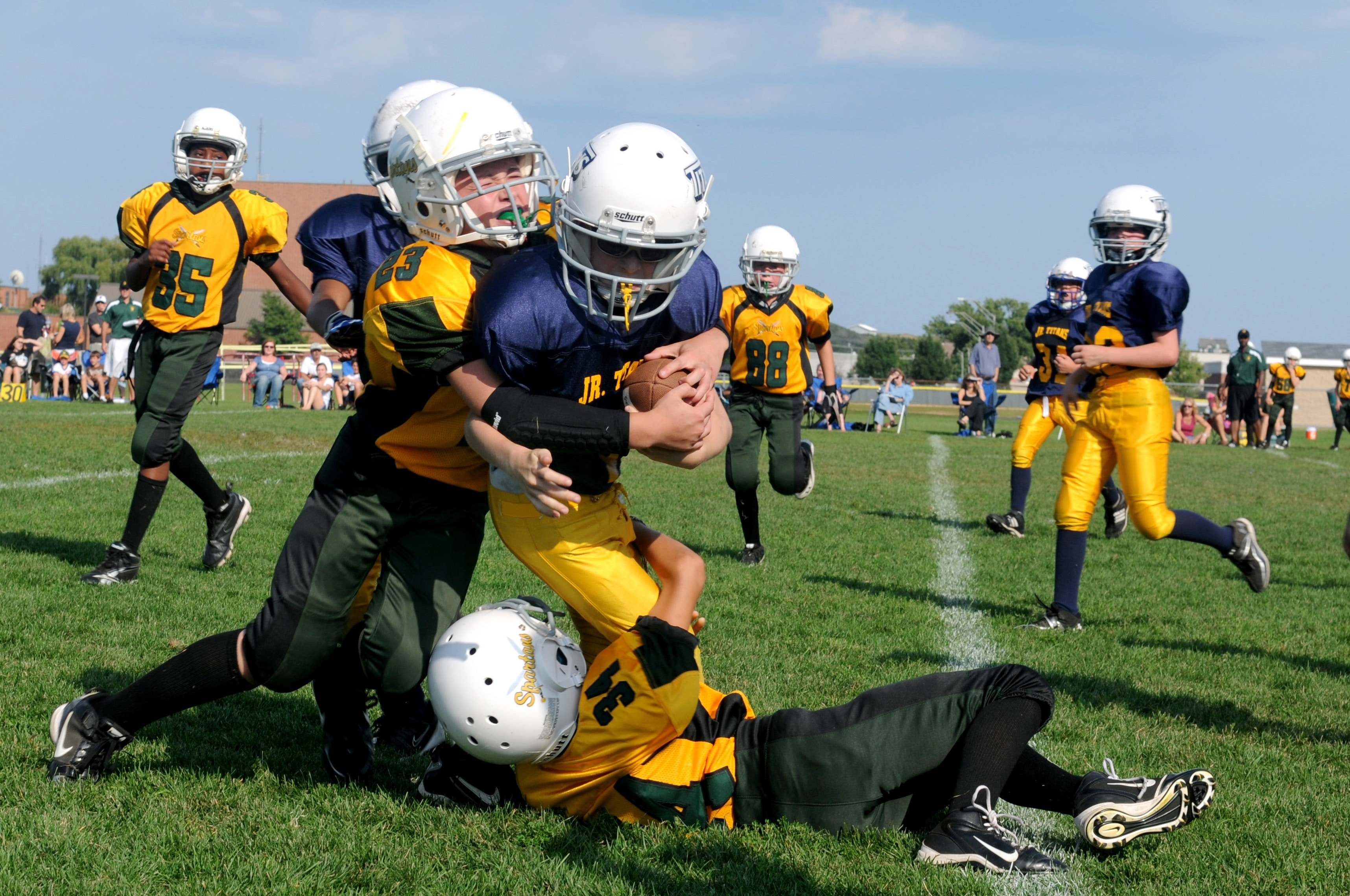 Boys participate in a game of tackle football on a lush green field.