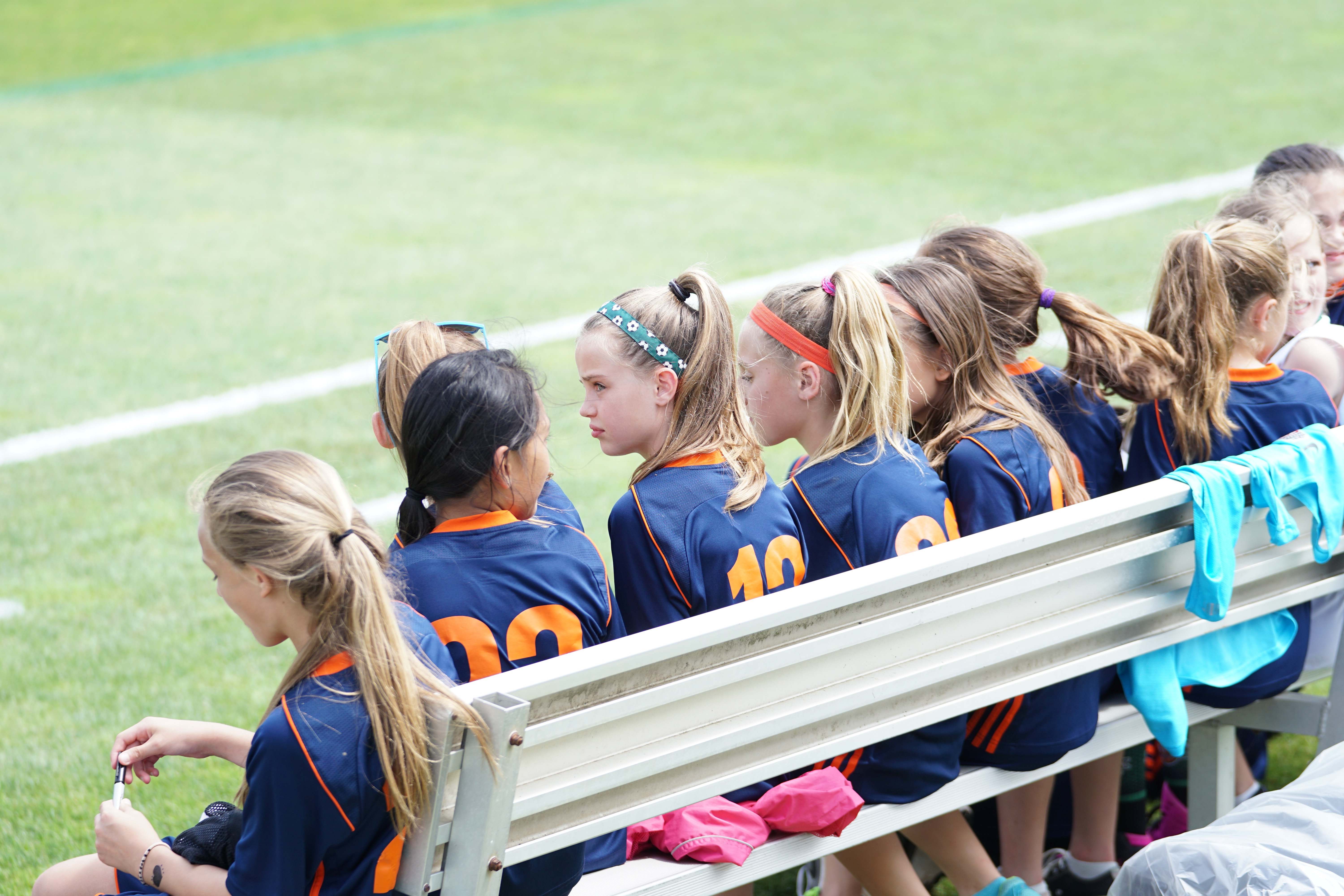 A girl's soccer team sits on a bench, awaiting kick-off.