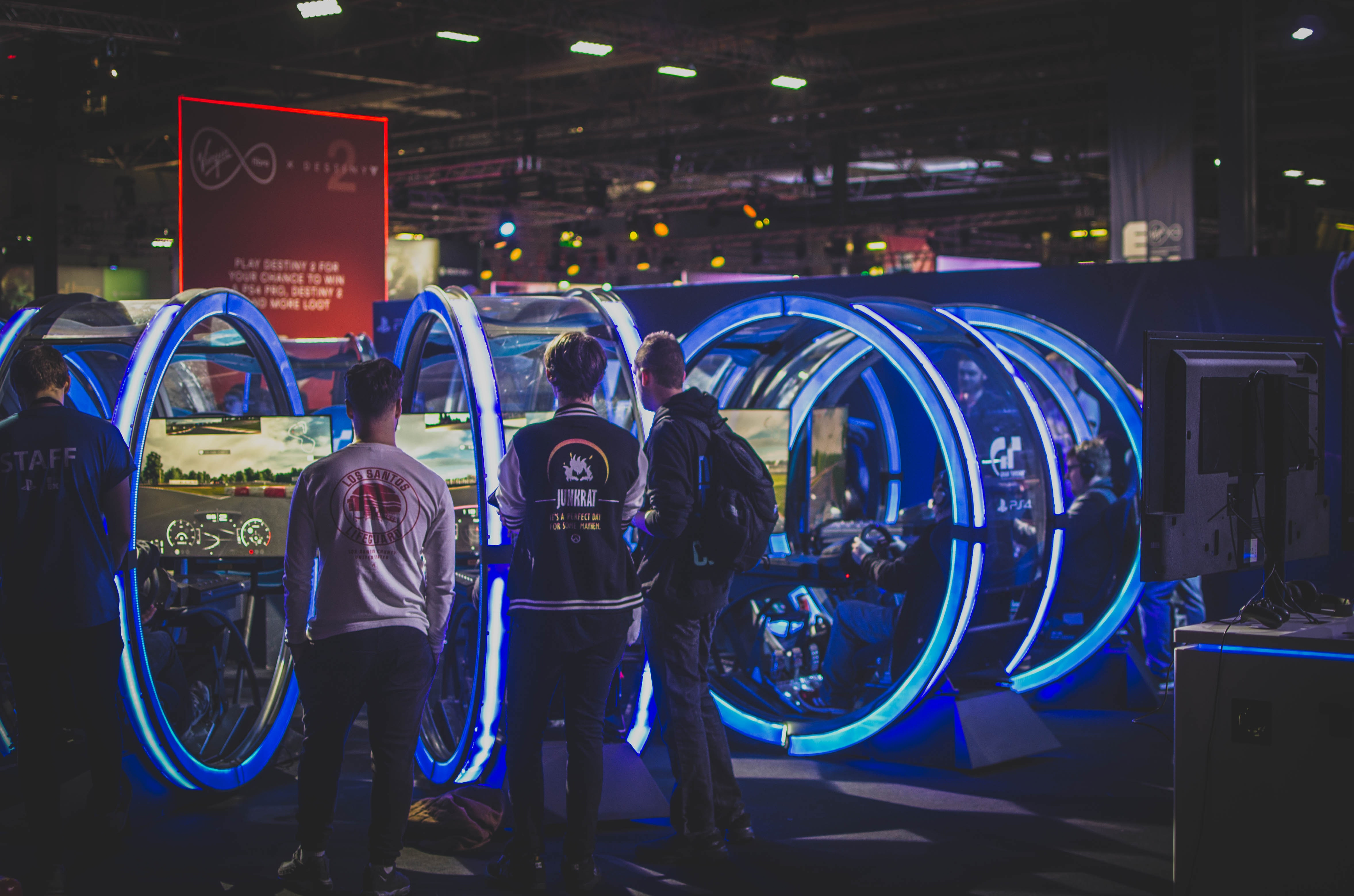 A group of e-athletes looks at a neon-lit racing arcade game