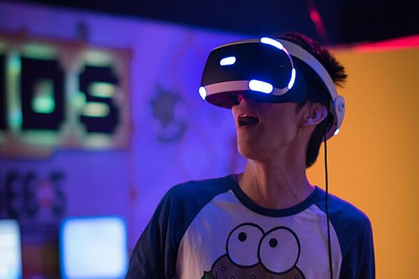 An e-athlete looks in awe at an esport game through a virtual reality console