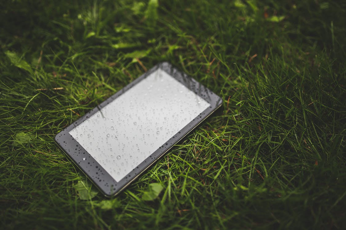 An iPad containing secure information lays unattended on a wet field