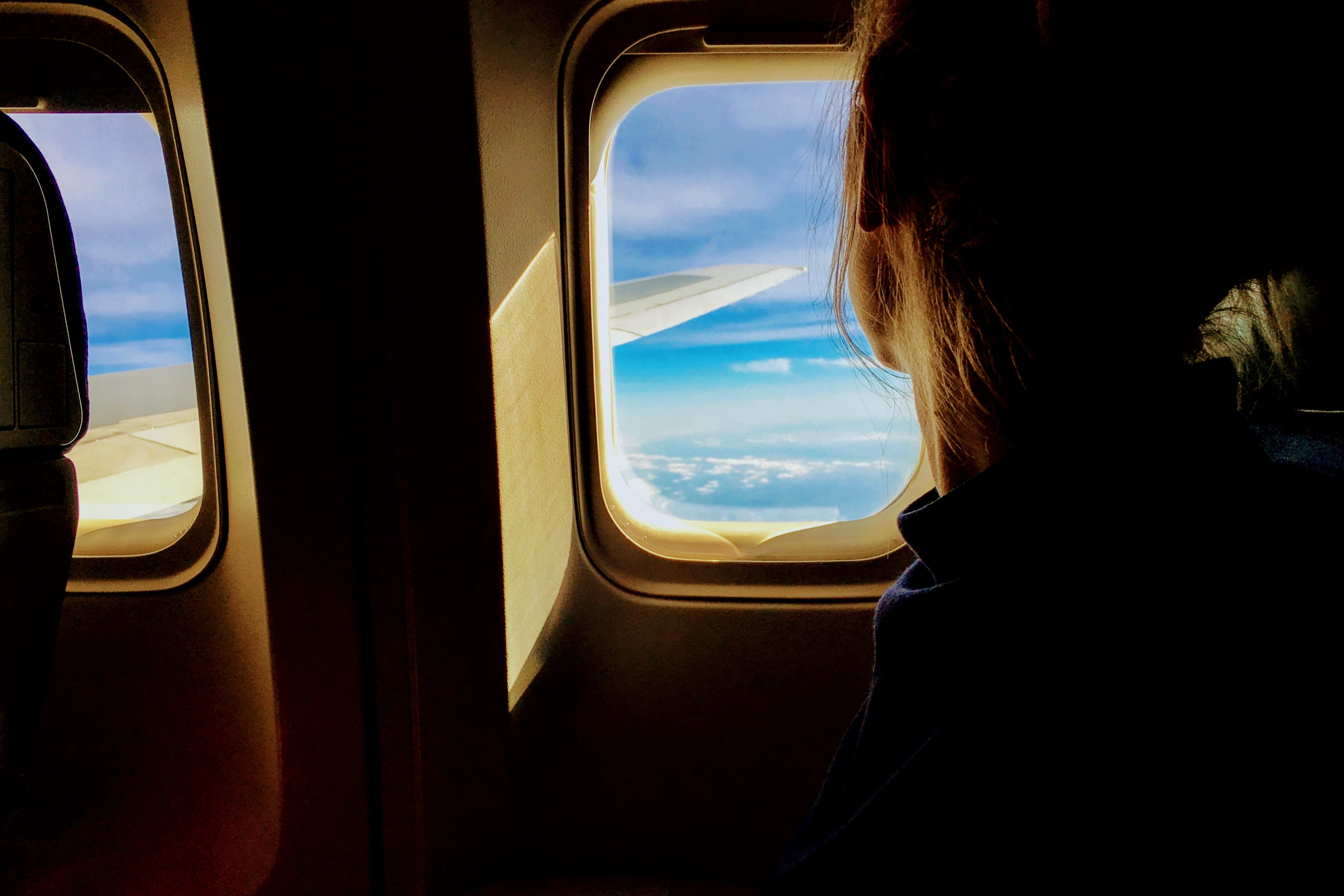 An athlete looks out the window of an aircraft, considering their destination timezone