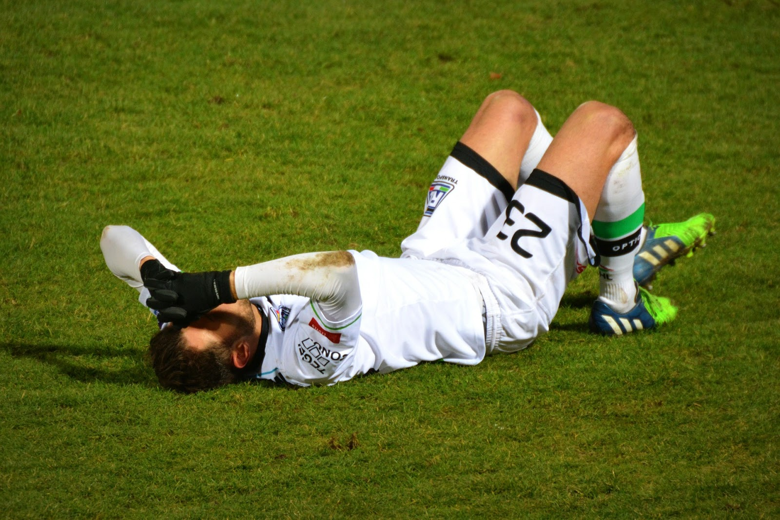 Soccer player lying on field trying to recover from concussion