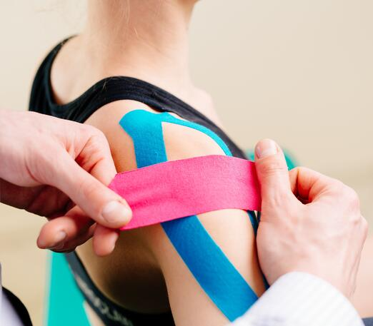 An athletic trainer taping an athlete's shoulder to help her play