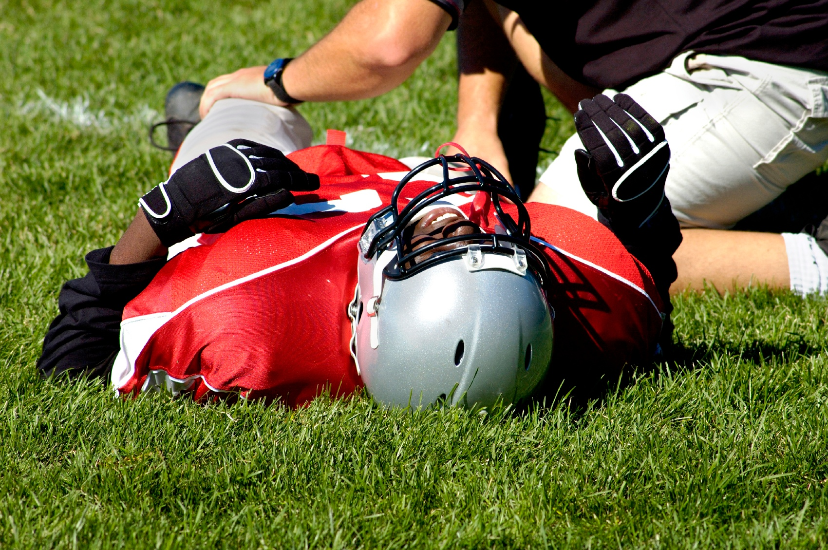 An AT who is showing the qualities of a successful athletic trainer by helping an injured football player