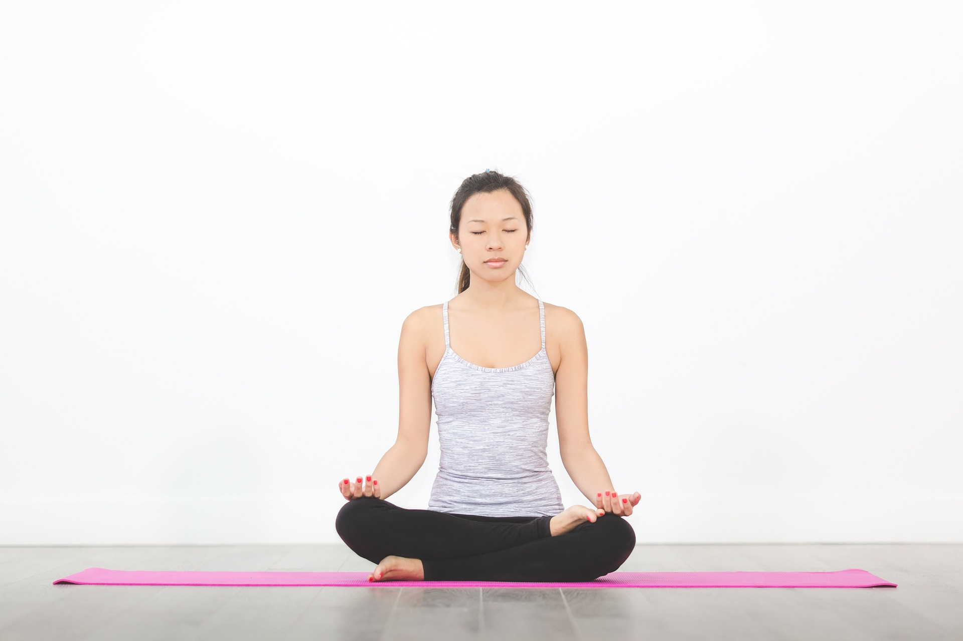 A female athlete sitting on a yoga map practicing mindful meditation